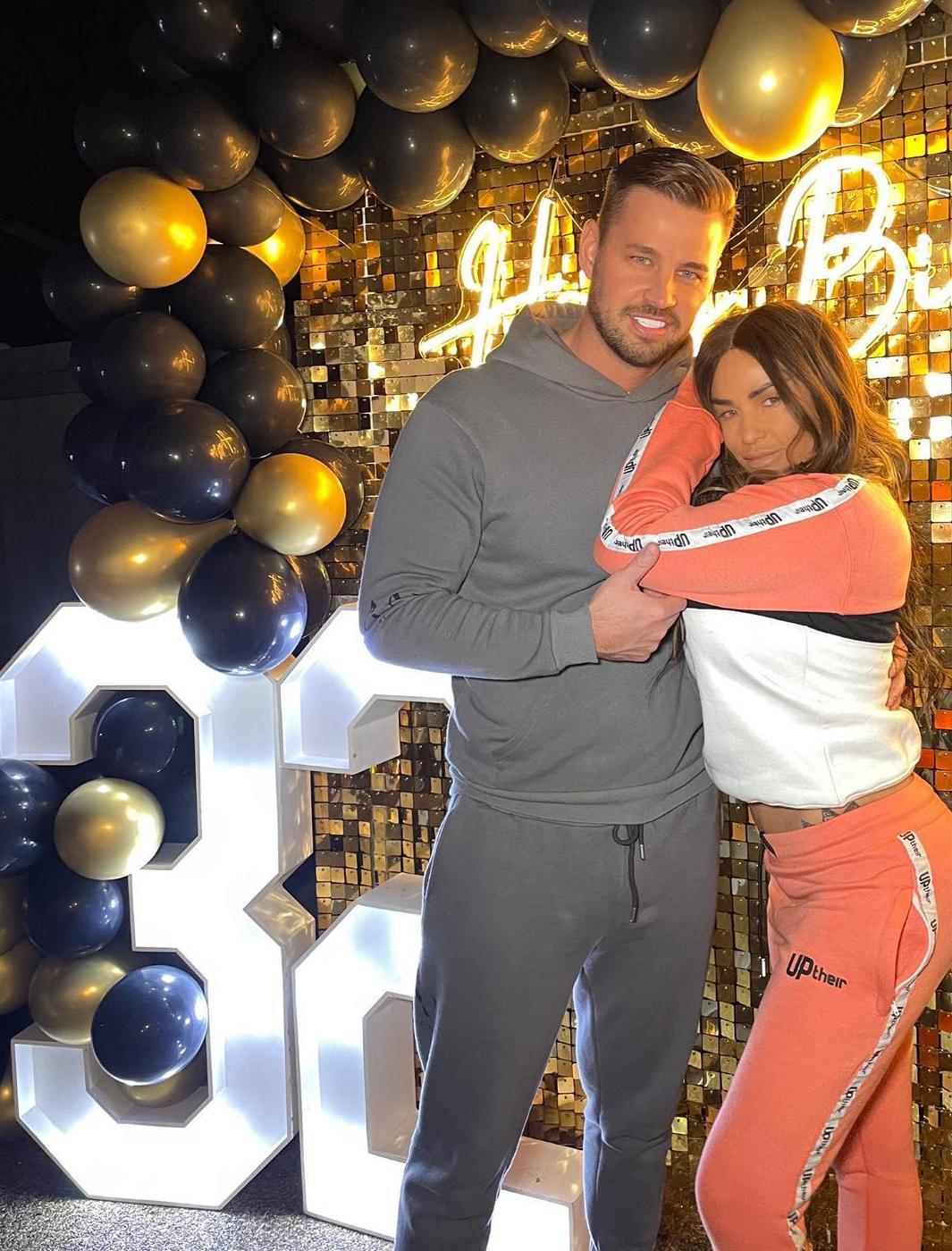 Katie Price wearing a peach Uptheir tracksuit hugging boyfriend Karl Woods in a grey tracksuit