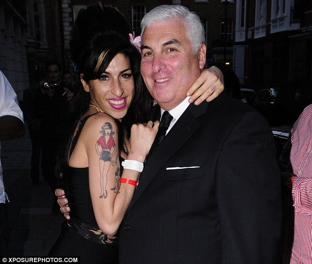 Mitch Winehouse in a suit hugging and Amy Winehouse wearing a black dress