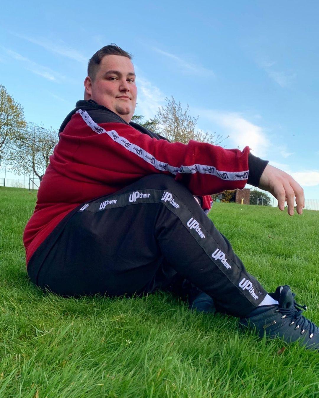 Steven Mckell sitting sideways on grass wearing black Uptheir tracksuit bottoms and red sweatshirt