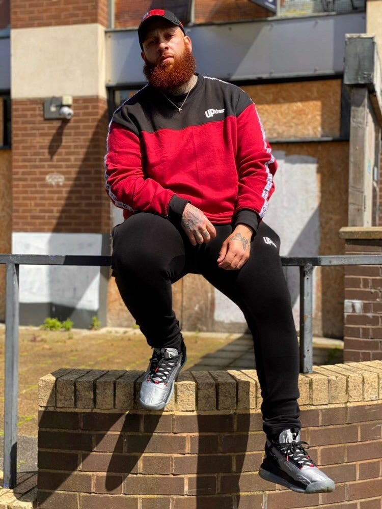man with beard sitting on wall wearing black Uptheir tracksuit bottoms and a red sweatshirt