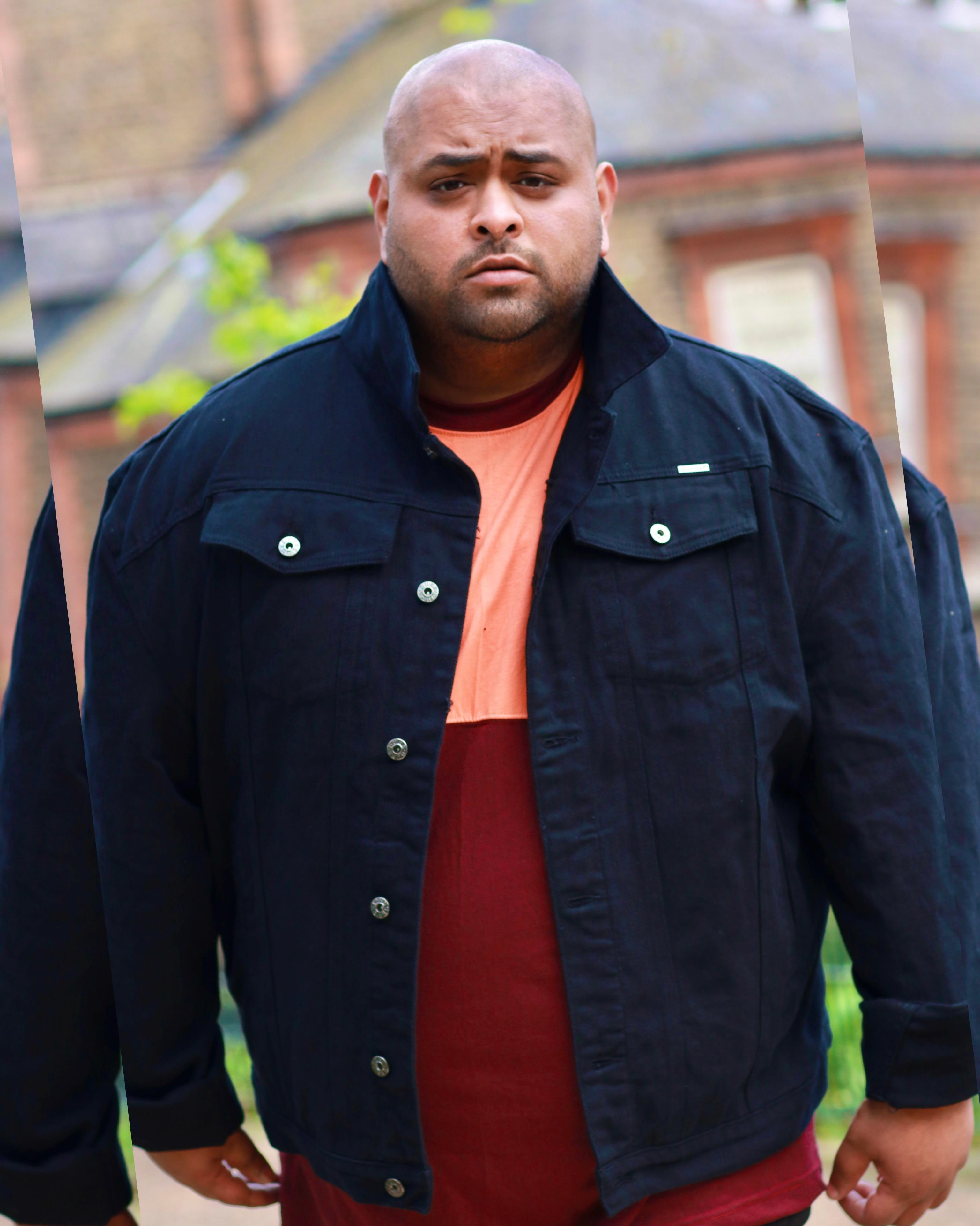 Influencer Sugapuff wearing a black denim jacket and red and orange t-shirt